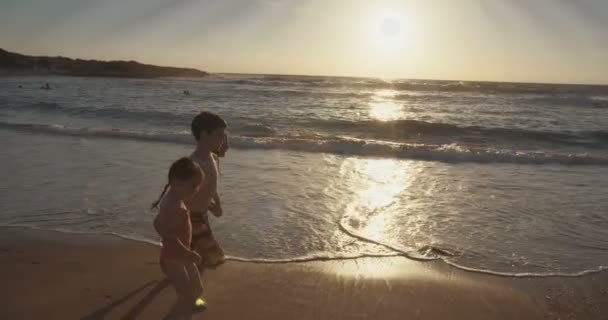 Three kids running and playing together at the beach during sunset