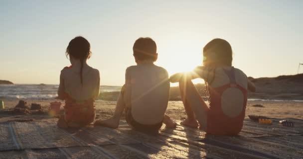 Tři děti jedí melouny na pláži při západu slunce