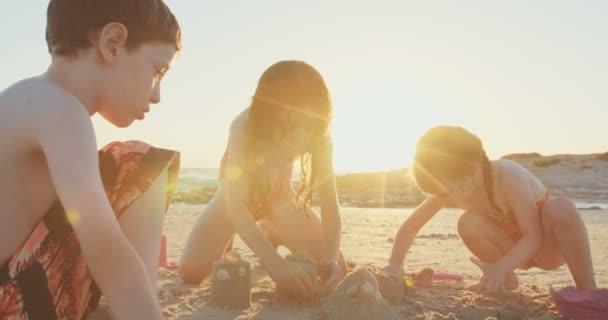 Tři děti, budování hrady z písku na pláži při západu slunce
