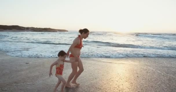 Mother and her daughter running on the beach at sunset