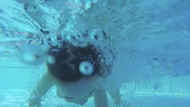 Underwater footage of a little girl playing and jumping in a swimming pool