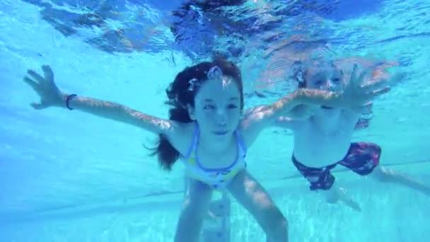 Podvodní záběr dvě děti skákání a potápění v bazénu