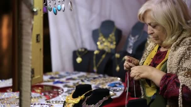 MURCIA, SPAIN-MARCH 5,2016: Woman-seller of handmade jewelry buttons chain in  a medieval market on March 5,2016 in Murcia,Spain.