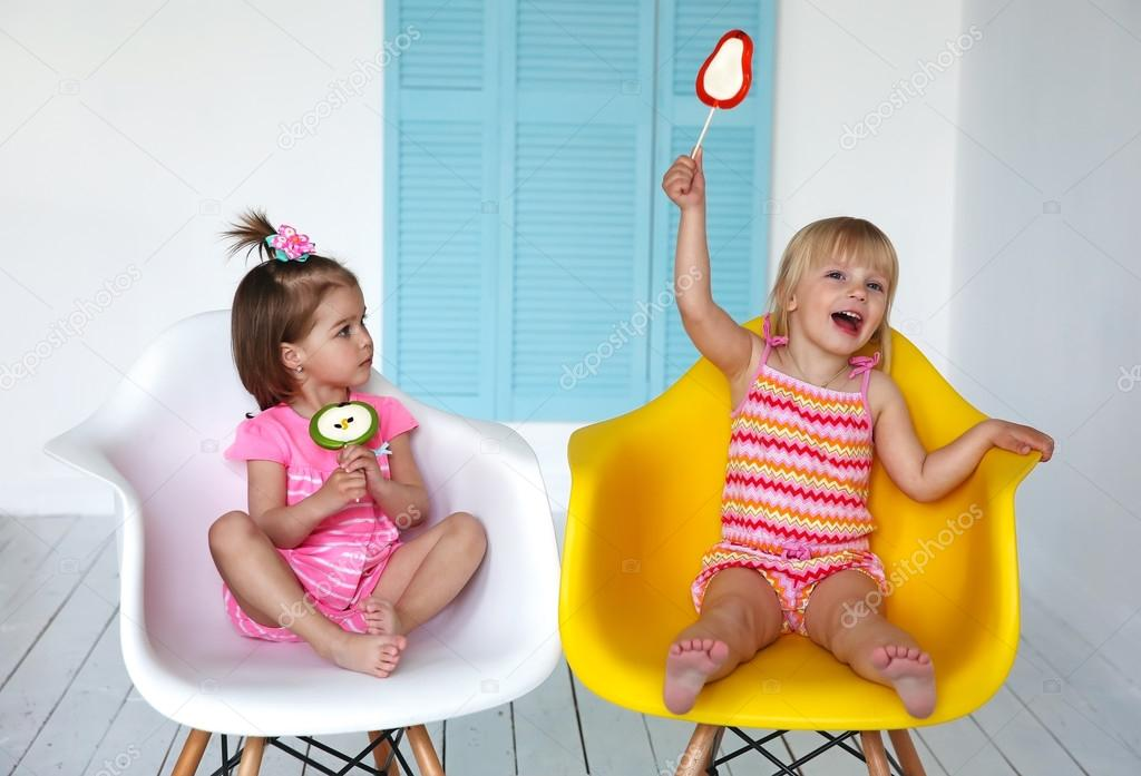 Little Girls Sitting In Chairs And Eating Candy Sticks U2014 Stock Photo