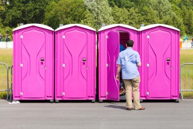 four portable toilets on a street