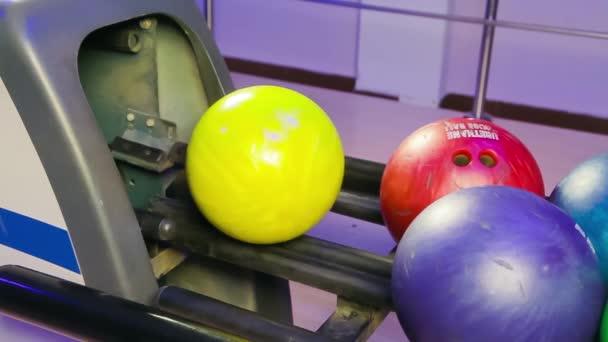 muž hodí bowlingovou kouli na hrací plochu a klepe kolíky