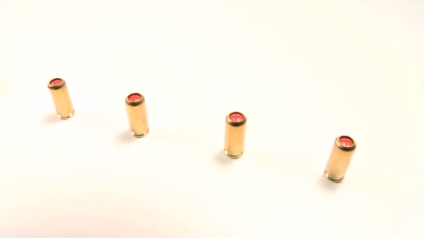 Line of pepper gas-cartridges and semi-automatic handgun, beauty-shot close-up on white background.