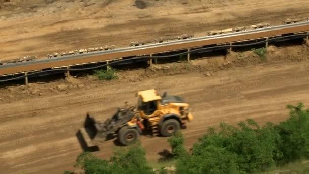 Povrchová těžba. Bagr jednotkám poblíž ploché dopravníku. Střední zásah. Povrchový důl