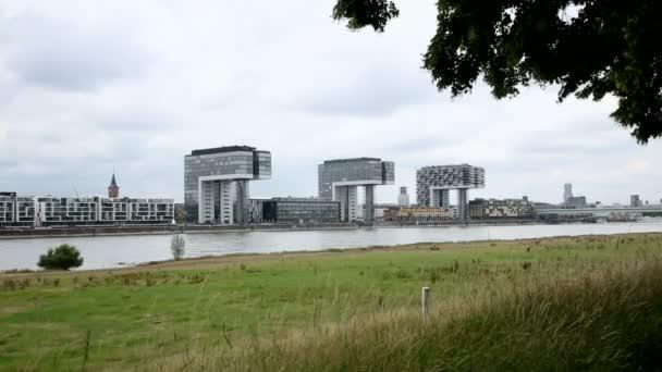 Kranhäuser. Kölns moderne Architektur verschwindet hinter Bäumen. Skyline. Kamerafahrt. Weitschuss.