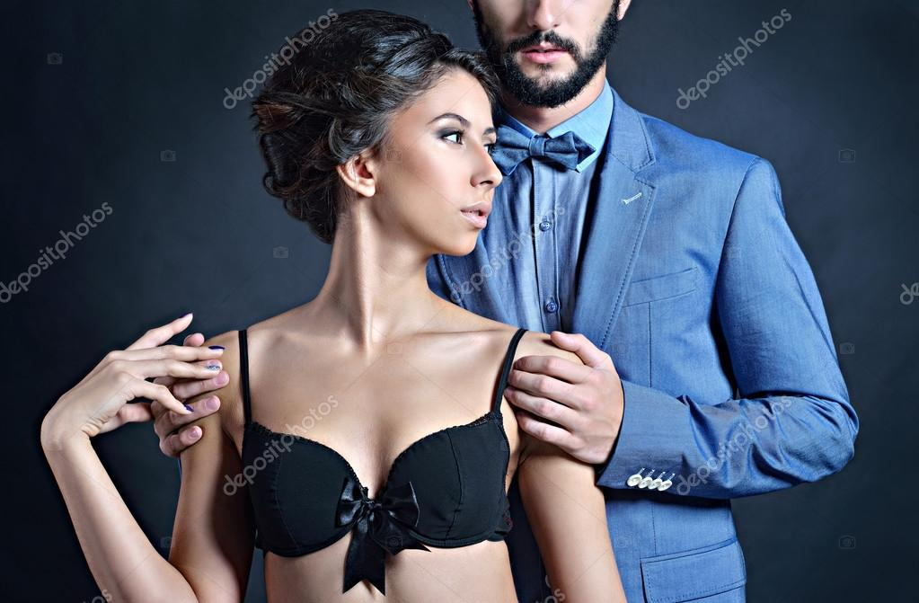 ca4f5e0ffc Beautiful lady in bra with handsome guy in suit. Young couple hugging.  Portrait of girl in underwear and boy indoors in passionate poses.