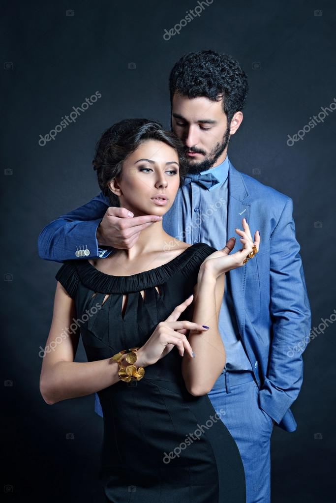 1a60b007fd Beautiful lady in black dress with guy in suit. Young couple hugging.  Portrait of girl and boy indoors in passionate poses — Photo by ...