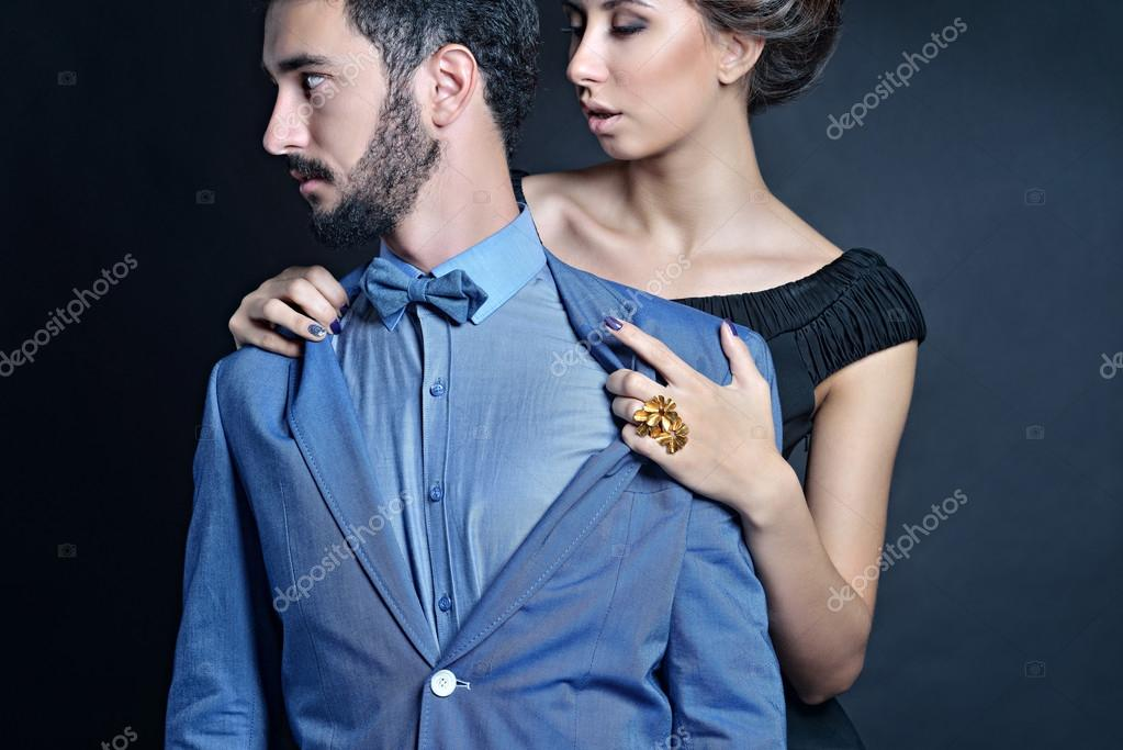 c68c252caf Beautiful lady in black dress with guy in suit. Young couple hugging.  Portrait of girl and boy indoors in passionate poses — Photo by pvstory