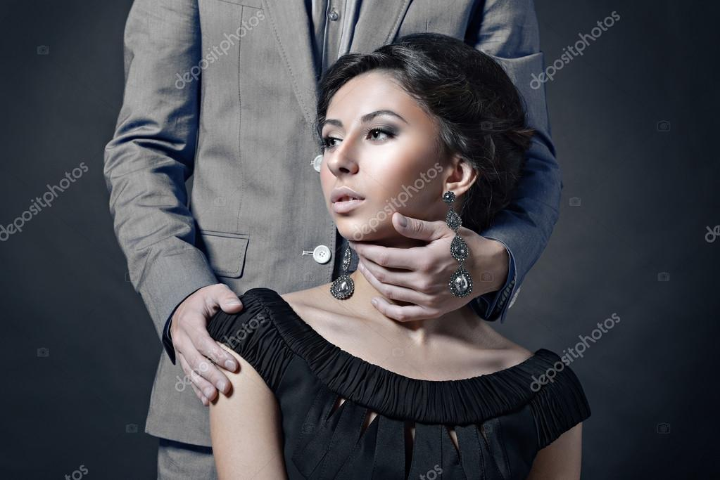 3d4e5bf3a3 Beautiful lady in dress with guy in suit. Young man hugging beautiful  brunette woman. Portrait of girl and boy indoors in passionate poses —  Photo by ...