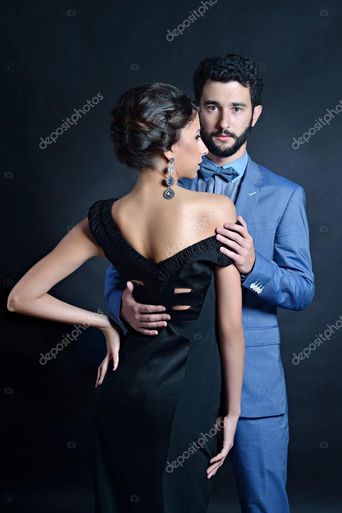 4731d9c881 Beautiful lady in dress with guy in suit. Young couple hugging each other.  Portrait of girl with attractive body and boy indoors in passionate poses  on dark ...