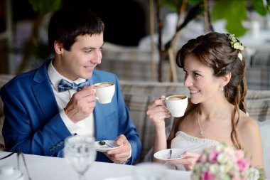 Wedding couple indoors drinking coffee. Beautiful girl in white dress. Man in suit. Beauty bride with groom. Female and male portrait. Cute lady and handsome guy stock vector