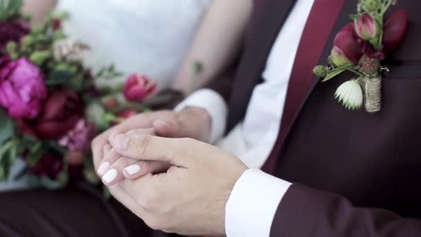 Svatební pár drží za ruce
