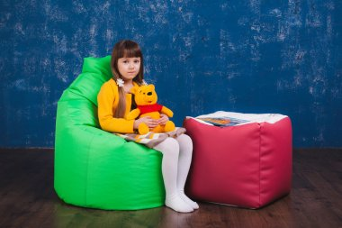 Cushioned furniture. A child with toys and books on a chair bag