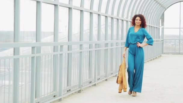 Beautiful curly-haired woman in a long dres