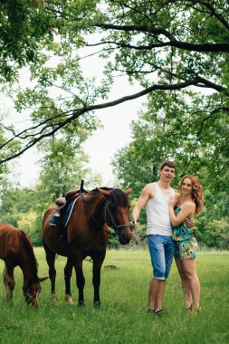 Lovers  on the background of horses