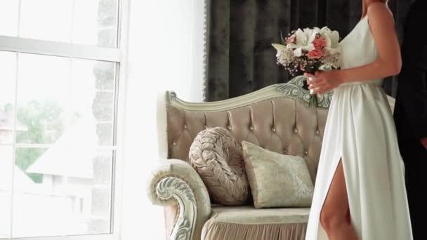 Gyönyörű virágcsokor egy fehér ruhás lány kezében.