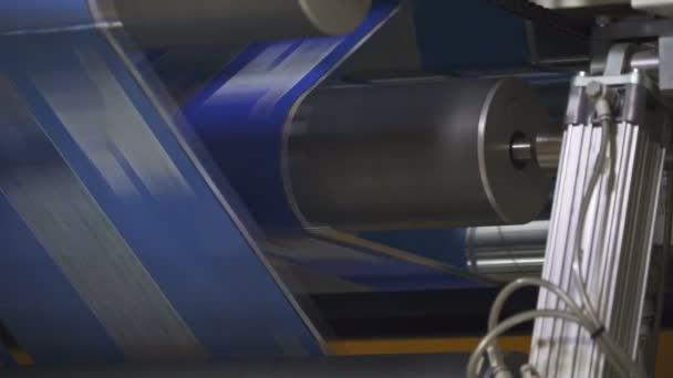 Tiskárna, flexotisk. film se točí mezi hřídelí. otisk stroje na kolečkách. hřídel se rychle otáčí. aniloxové hřídele