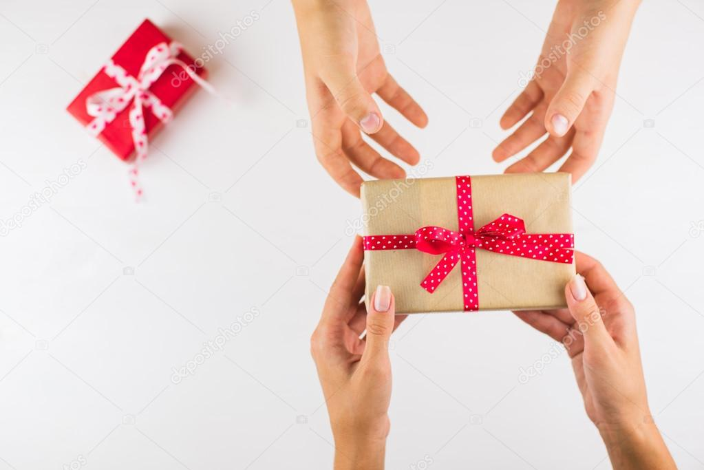 Closeup of hands giving gifts to each other on white background closeup of hands giving gifts to each other on white background stock photo negle Images