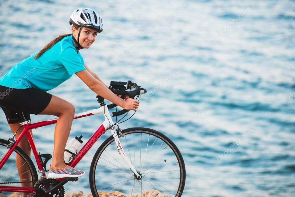 Female cyclist riding bike with sea on background a happy female cyclist in helmet riding her bike with sea on background adventures and active lifestyle bobakphotoail voltagebd Image collections