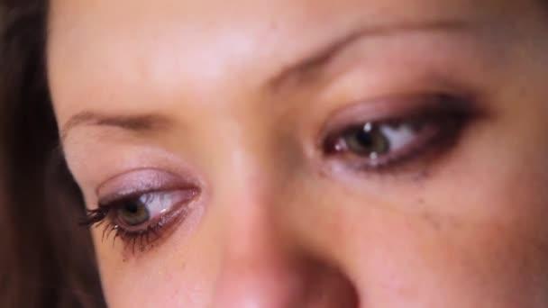 Közeli kép a lány könnyes szemmel. Piszok a tinta az arcon.