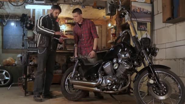 Mann spricht von Motorrad mit Automechaniker in Garage
