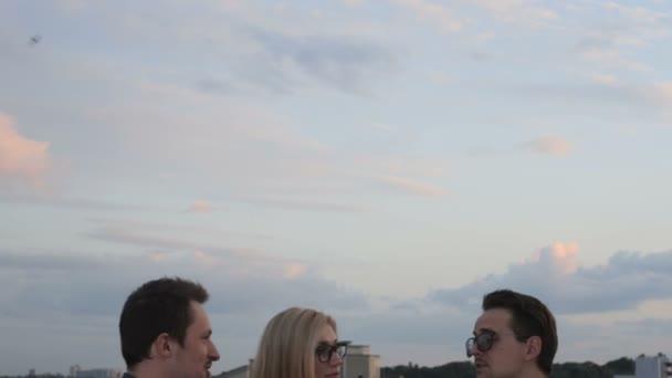 Lidé a na střeše úřední budovy na letní večer