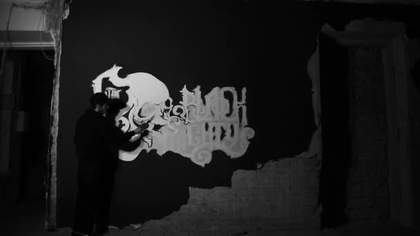 Malba bílá streetart umělec s lebkou na stěně černá