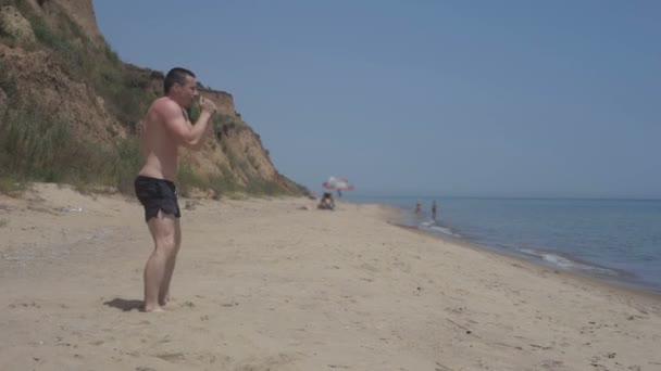 Man workout on sea beach on sunny summer day