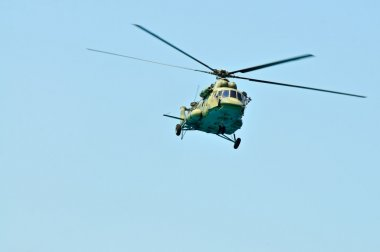 Military khaki helicopter flies against the blue sky