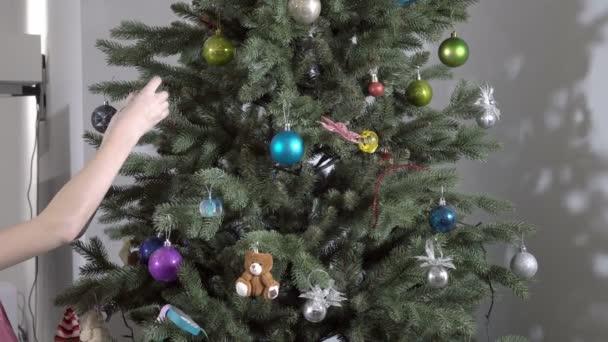 Malá holka zdobí vánoční stromek s vánočními hračkami doma. Detailní záběr dětských rukou. Koncept Vánoc. Bez tváře. 4K.
