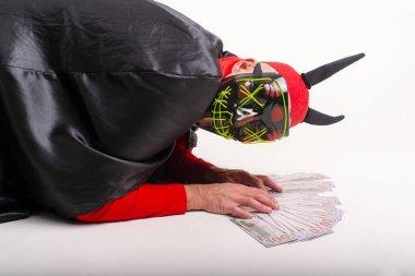 Maskeli adam, şeytan boynuzlu kırmızı şapkalı ve cadılar bayramı kostümlü beyaz stüdyo arka planında bir sürü parayla poz veren..