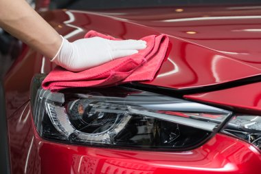 Car detailing series : Worker cleaning red car