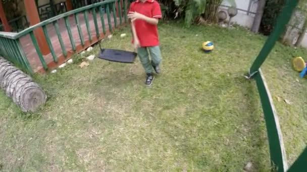 Roztomilé dítě na houpačce. Otec pomáhá syn jezdit na houpačce na dětské hřiště. Zpomalený pohyb portrét legrační obličej
