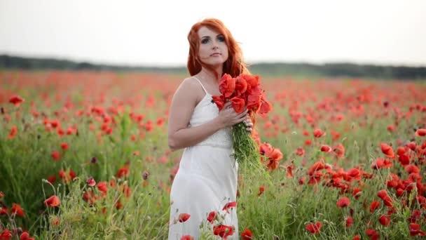 krásná mladá žena v makovém poli drží kytici mák
