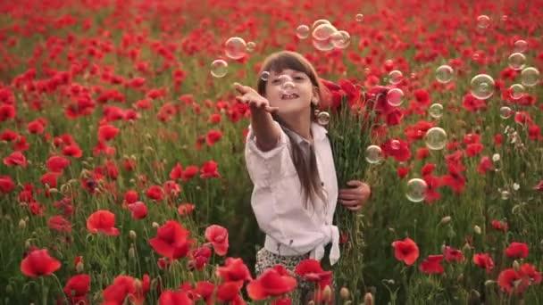 Malá usmívající se dívka chytí mýdlové bubliny v kvetoucím poli červených máků, zpomalení