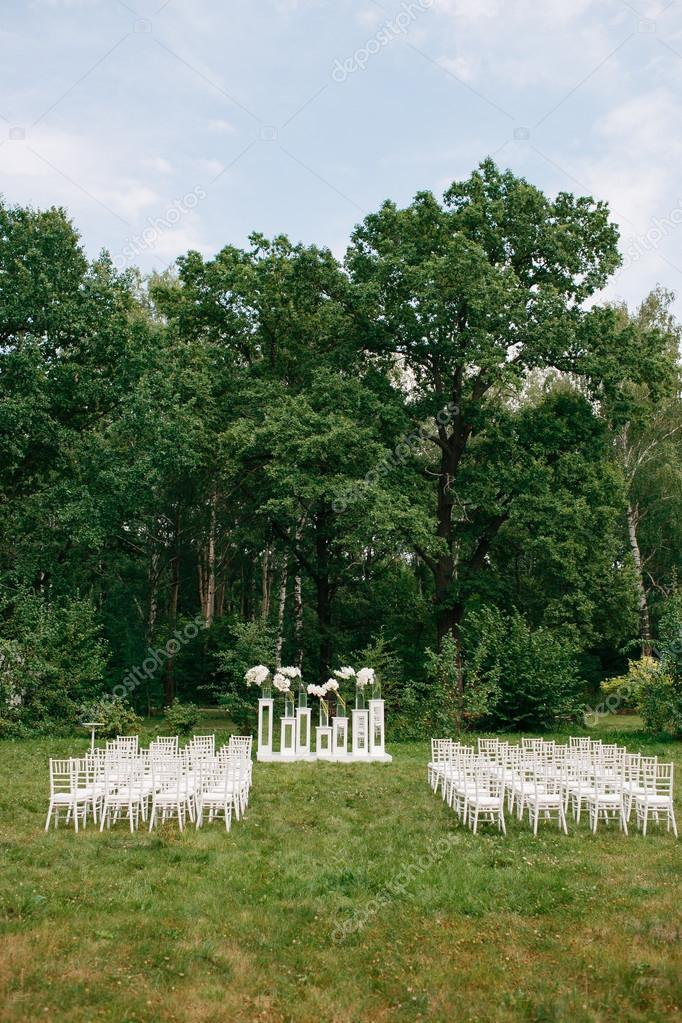 wedding ceremony in a beautiful garden. white chairs and mirrored tables. Glass vase with flowers calla lilies amaryllis