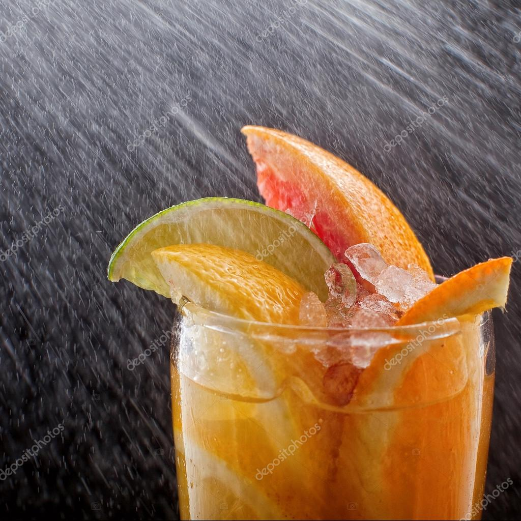 Chilled soft drinks with ice, citrus fruits and berries, black background, selective focus drop
