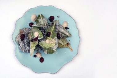 Fresh salad with sauce on plate, white background