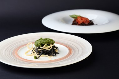 Two plates of black and white spaghetti with different sauces