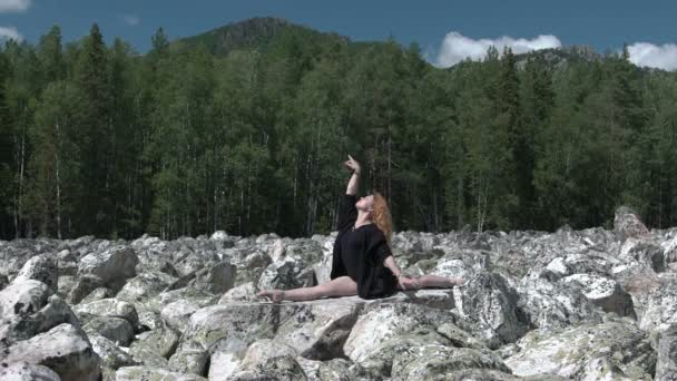 Mädchen macht Yoga auf den Felsen