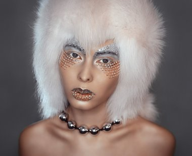 Girl's close portrait with rhinestones in a white fur hat and metal beads