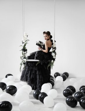 Gothic girl in black dress on the swing among the black and white balloons