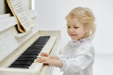little girl with a piano