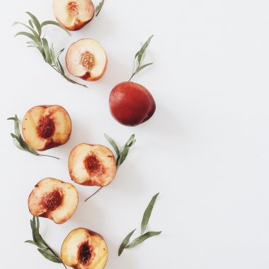 Peaches with leaves on white