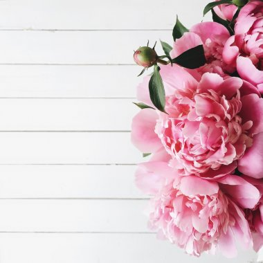 Overhead view of bouquet of pink peonies on white wooden background