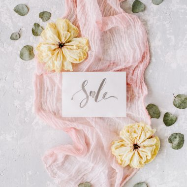Paper blank with word sale, dry white tulips, eucalyptus petals and pink textile on concrete background. Flat lay, top view stock vector